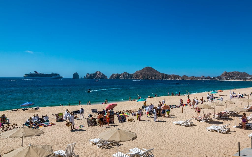 Vendors sell there wares and services to tourists in front of a resort in Cabo San Lucas as a cruise ship enters the bay.
